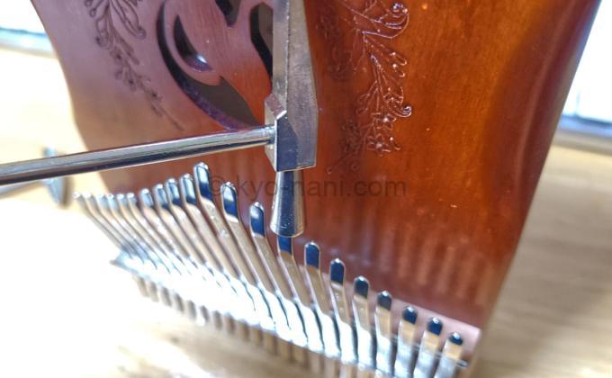 カリンバをチューニング用ハンマーで調律している写真