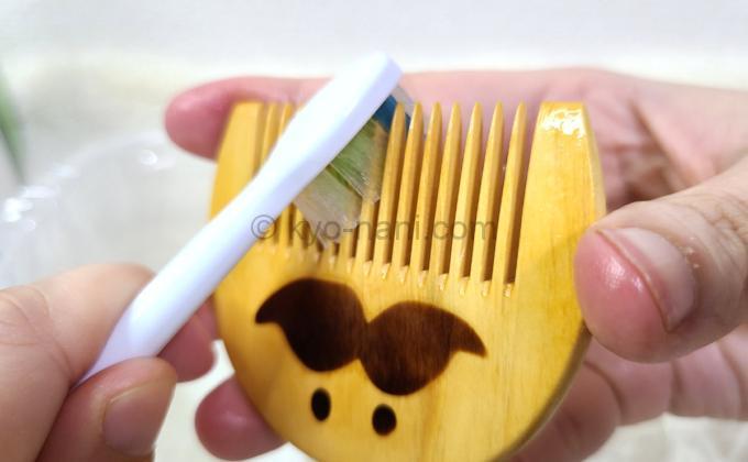 つげさん櫛(つげ櫛)の歯にに歯ブラシで椿油を塗っている写真